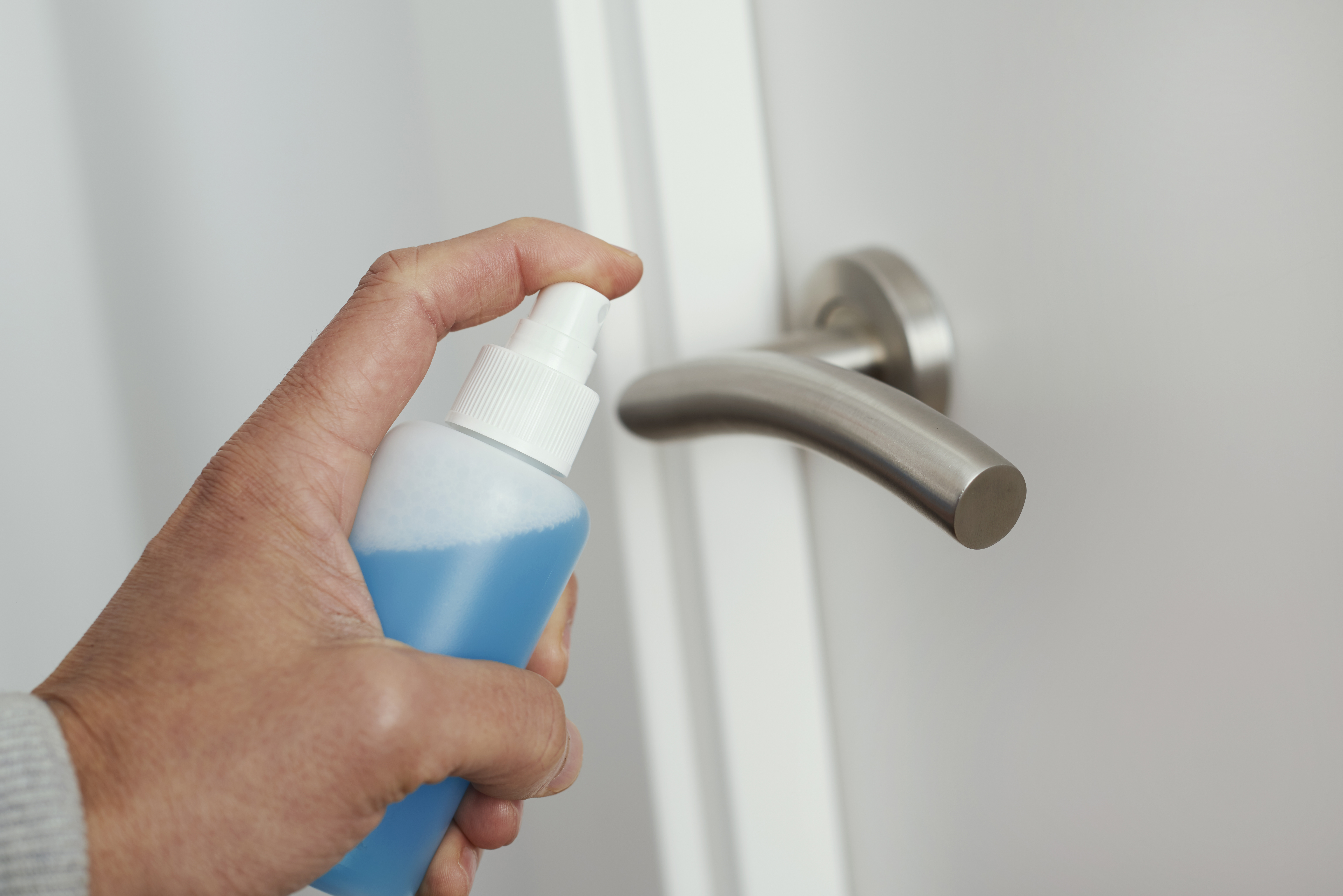 closeup of a caucasian man disinfecting the door handle by spraying a blue sanitizer from a bottle